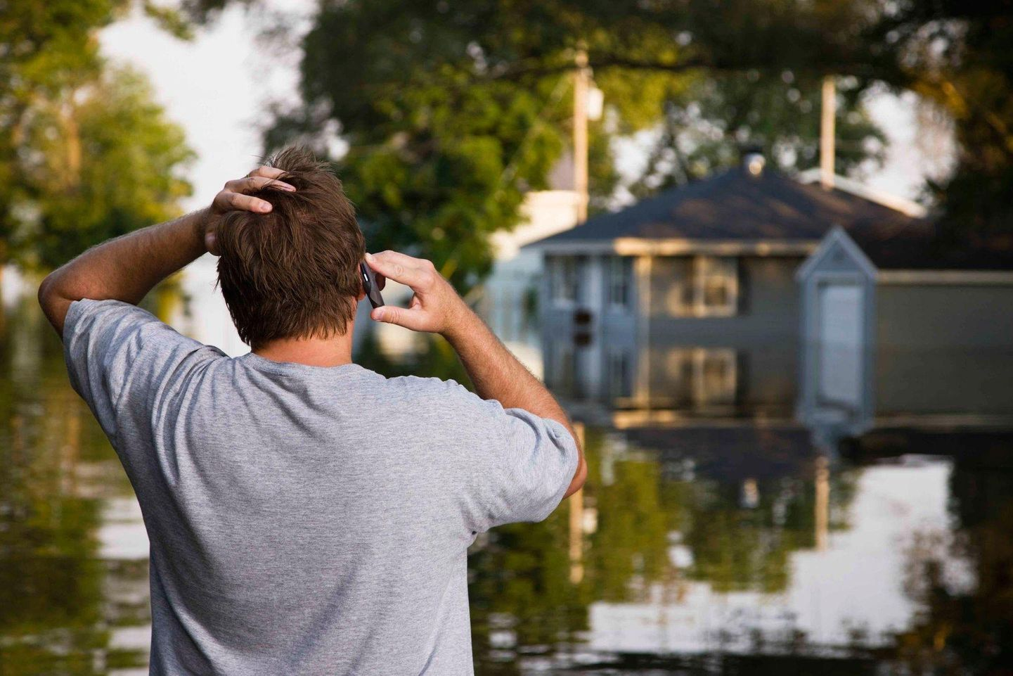 Man looking at his flooded house and making a phone call