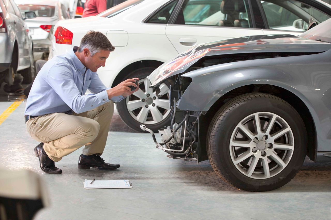 Claims adjuster checking front-end damage on a car.