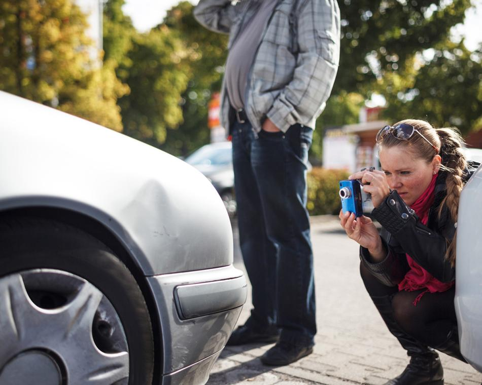 Claims adjuster inspecting damaged car