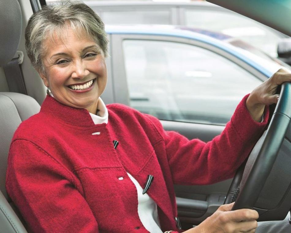 Woman in red jacket smiling as she sits at the wheel of her car.