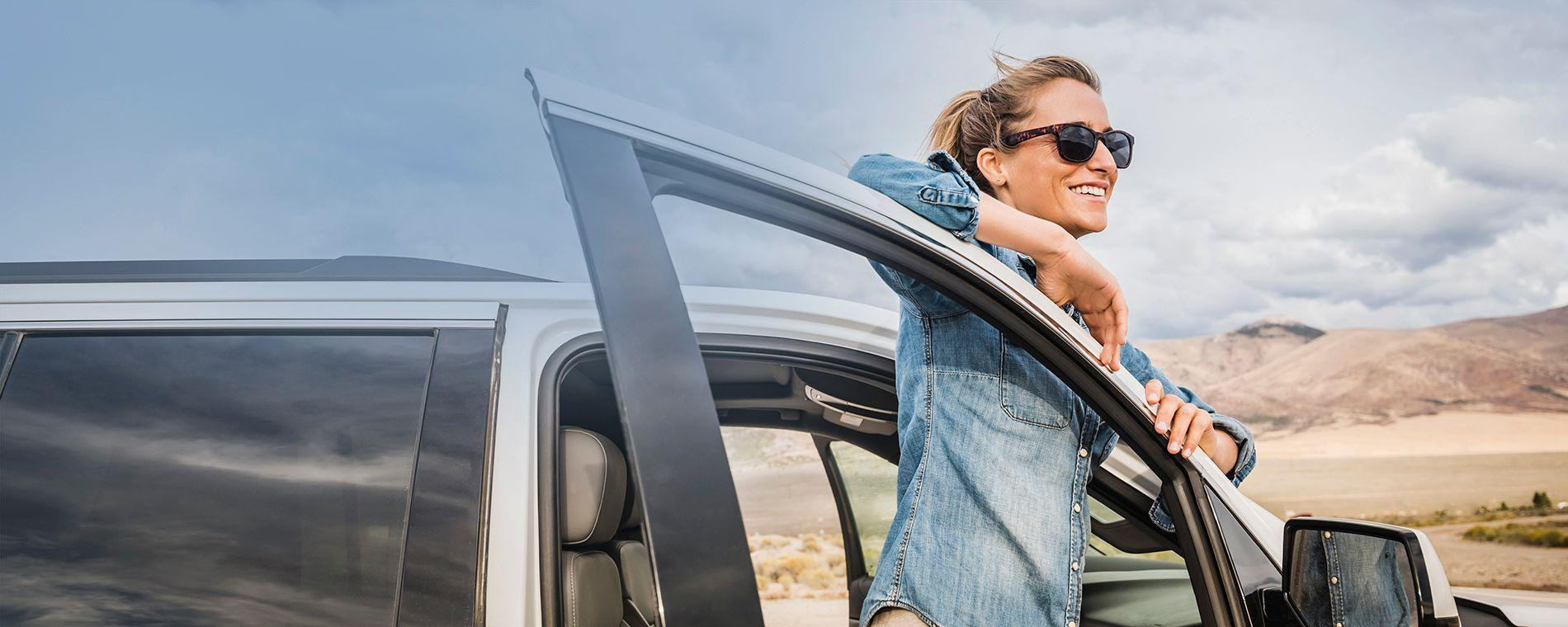 Smiling woman in blue shirt leaning on car door as she looks out over the beach.