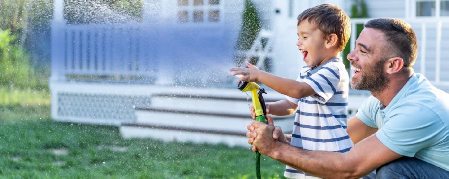 Photo of father and young son playing with a hose.